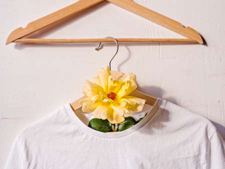 Creative floral background. A white cotton T-shirt is hung on a wooden coat hanger and decorated with a yellow flower. Fashionable layout.