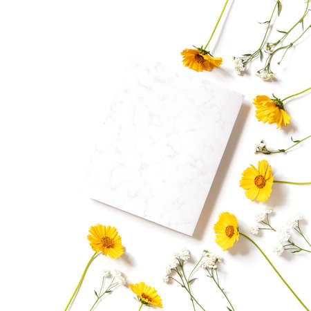 Flower composition. A template from a sheet of paper with a marble pattern is on a white background. Nearby are yellow flowers. Social media background. Holiday layout. Flat lay, copy space.
