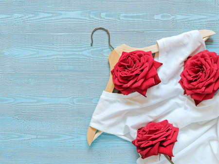 Flower composition. Layout of a wooden hanger, white cotton T-shirt and red roses. Blue wooden background. Template for sales, discounts, a new collection of clothes. Flat lay. Top view. Copy space. Stock fotó