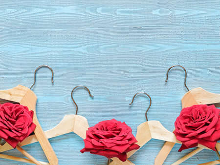 Flower composition. Layout of wooden coat hanger and red roses. Blue wooden background. Template for sales, discounts, a new collection of clothes. Flat lay. Top view. Copy space.