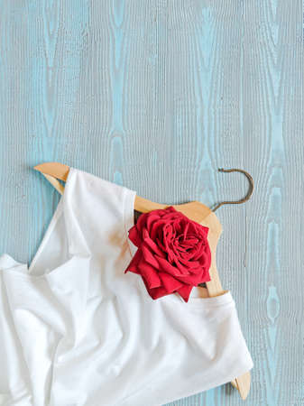 Flower composition. Layout of a wooden hanger, white cotton T-shirt and red roses. Blue wooden background. Template for sales, discounts, a new collection of clothes. Flat lay. Top view. Copy space. Reklamní fotografie