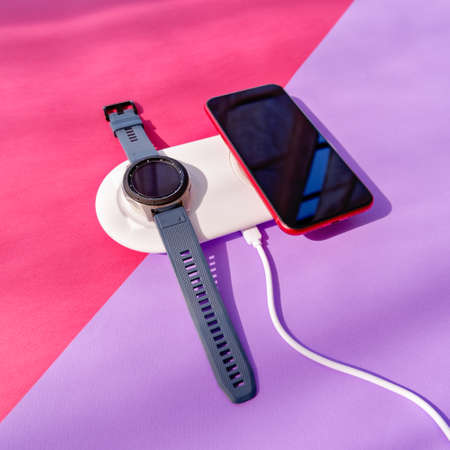 The concept of wireless charging of mobile gadgets. The smartphone and smartwatch are on the wireless charging pad. Colored paper background. Flat lay.