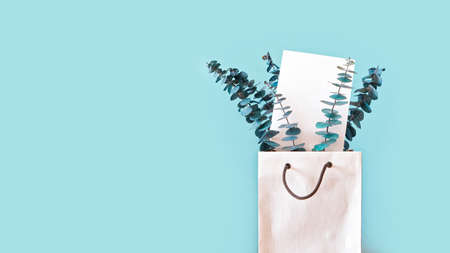 Eucalyptus branches are in a white paper bag with handles. There is an empty piece of paper among the leaves. Decor concept for living quarters, shops or offices. Copy space.