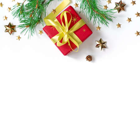 The gift wrapped in red wrapping paper is tied with a yellow ribbon with a bow. Natural pine branches, cones and gold stars are on a white background. Christmas composition. Flat lay. Copy space Stock fotó