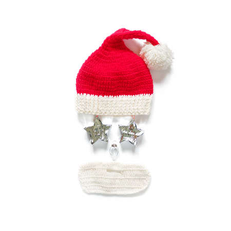 Funny Christmas composition. Knitted hat and beard and Christmas decorations in the form of the face of Santa Claus are on a white background. New Year, winter concept. Flat lay. Top view. Stockfoto