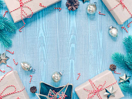 Christmas composition. Gifts in craft paper are tied with a striped ribbon. Coniferous branches, cones and decorations are nearby. Blue wooden background. Flat lay, top view, copy space.