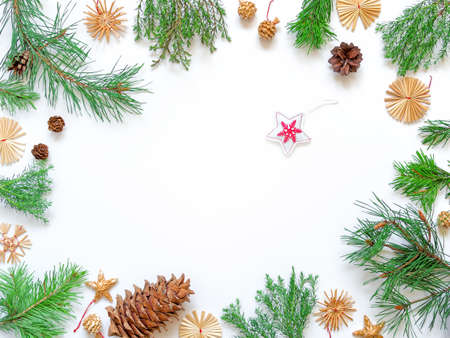 Christmas composition. Fabric star, straw decorations, pine cone are on a white background. The mockup is framed by sprigs of coniferous plants. New Year concept. Flat lay. Top view. Copy space. Stock fotó