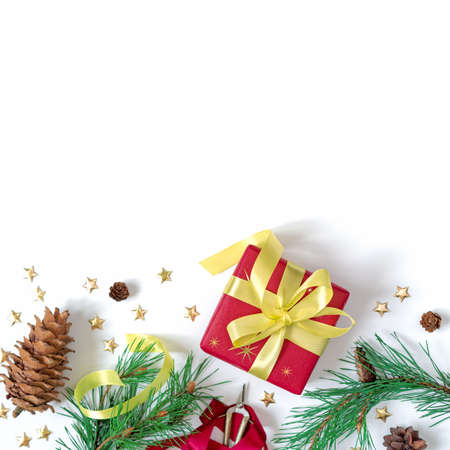 The gift wrapped in red wrapping paper is tied with a yellow ribbon with a bow. Natural pine branches, a pine cone and gold stars are on a white background. Christmas composition. Flat lay. Copy space Stock fotó