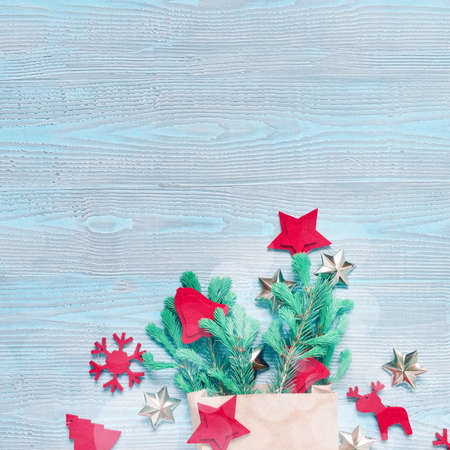 Christmas composition. Natural coniferous branches are in a paper bag. Nearby are red felt decorations, glass balls and golden stars. Blue wooden background. Flat lay, top view, copy space