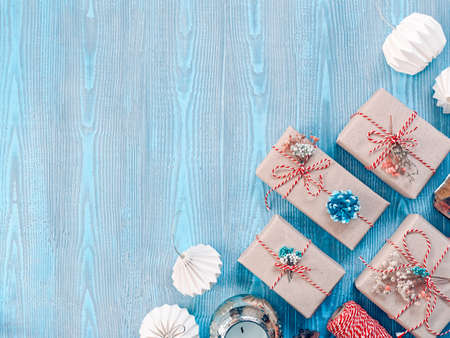 Christmas composition. Gifts in craft paper are tied with a striped rope. The boxes are decorated with dried plants. Nearby are paper decorations, a spool of thread and a candle. Wooden background. Stock fotó