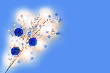 Christmas composition. A snow-covered branch with white berries is illuminated by an electric garland. The background is decorated with figures of snowflakes. Flat lay, top view, copy space.
