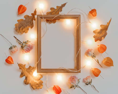 Creative autumn layout. An empty wooden photo frame is illuminated with a glowing garland. The template is decorated with dried oak leaves and flowers. Flat lay. Copy space