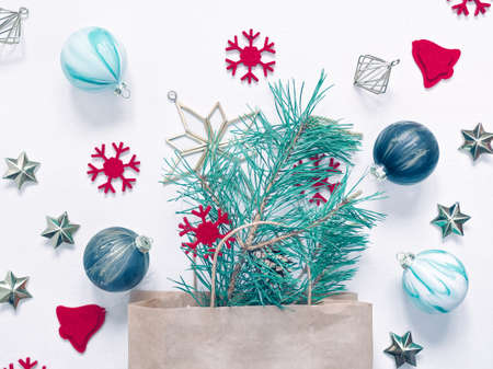 Christmas composition. Natural pine branch with needles is in a paper bag with handles. There are Christmas decorations and red felt figures nearby. Flat lay. Top view.
