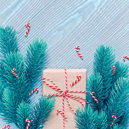 Gift wrapped in craft wrapping paper will be tied with striped ribbon. Blue wooden background decorated with coniferous branches with candy canes. Flat lay. Top view. Copy space.