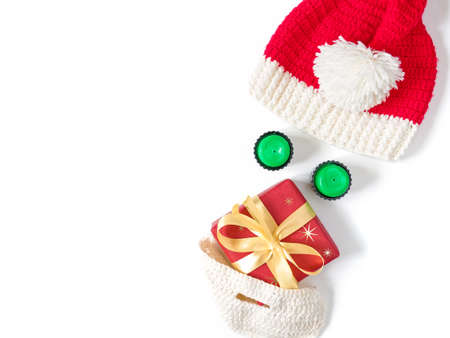 Fun Christmas composition. A knitted hat and beard, green candles and a gift wrapped in red paper are in the form of the face of Santa Claus. Flat lay, top view, copy space. Stock fotó
