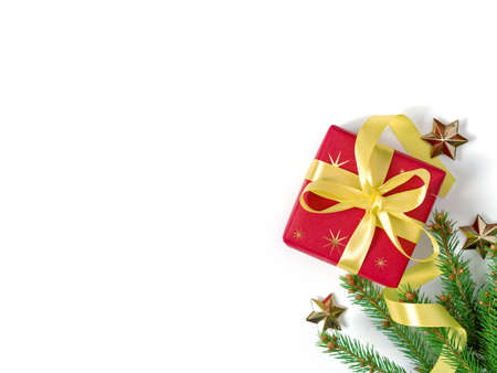 The gift wrapped in red wrapping paper is tied with a yellow ribbon with a bow. A natural spruce branch and golden stars are nearby. Christmas composition. Flat lay. Top view. Copy space.