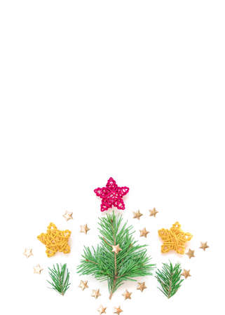 Christmas composition. A natural green coniferous twig and a red braided star ornament are on a white background. New Year, winter concept. Greeting card. Flat lay, top view, copy space.