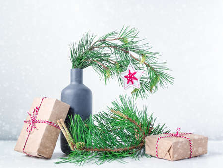 Christmas composition. The natural pine branch is decorated with a Christmas star decoration and is in a gray bottle. Nearby are gifts wrapped in craft paper and tied with a striped string. Stock fotó
