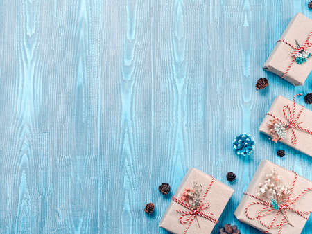 Christmas composition. Gifts in craft paper are tied with a striped rope. The boxes are decorated with dried plants. There are cones nearby. Blue wooden background. Flat lay, top view, copy space. Stock fotó