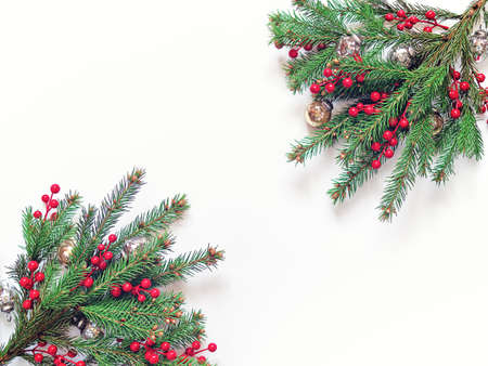 Christmas composition. Fir branches decorated with red berries and golden glass balls are on a white background. New Year, winter concept. Flat lay. Top view. Copy space.