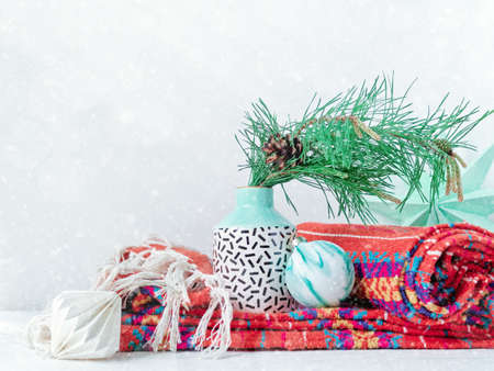 Christmas composition. A vase with a natural pine branch is in a vase on a knitted blanket. There are Christmas decorations nearby. New Year concept. Copy space. Stock fotó