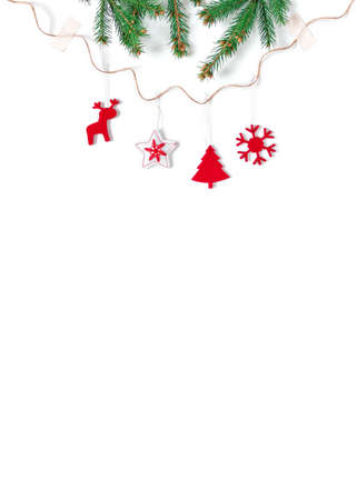 Christmas composition. The layout is made of red felt decorations and coniferous branches. White background. New Year, winter concept. Flat lay. Top view. Copy space.