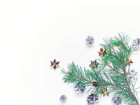 Christmas composition. Pine branches with soft green needles are on a white background. There are silver cones and golden stars nearby. New Year, winter concept. Flat lay. Top view. Copy space.