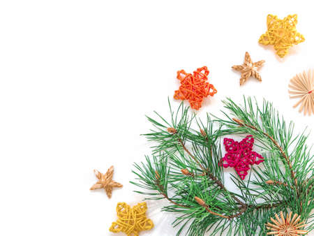 Natural pine branch with green needles is decorated with multi-colored braided stars and straw decorations. Christmas composition, greeting card. Flat lay, top view, copy space.