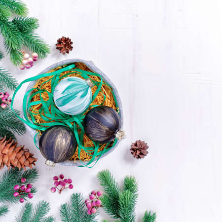 Christmas composition. The painted Christmas balls are in a felt basket. Fir branches, cones and berries are nearby. The concept of preparing for the new year. Flat lay. Top view.