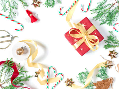 Christmas layout. The gift wrapped in red wrapping paper is tied with a yellow ribbon with a bow. Red cloth figurine of an angel, green coniferous twigs and decorations are on a white background.