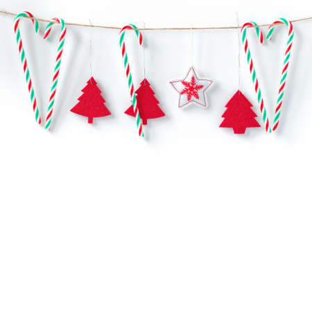 Red felt decorations and candies hang from the rope. White background. Christmas, New Year, winter concept. Copy space. Stock fotó