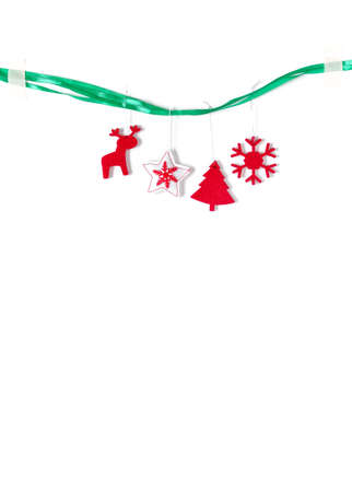 Red felt Christmas decorations hang on a green ribbon on a white background. Christmas, New Year, winter concept. Copy space.