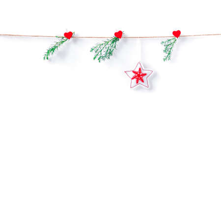 A star made of white fabric with a red Christmas pattern hangs on a rope. Coniferous branches are suspended nearby. Christmas, New Year, winter concept. Copy space.