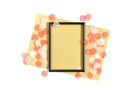 Abstract template in a minimalistic style. Blank black photo frame and a sheet of yellow paper will be found on a white background. The mockup is decorated with round confetti. Flat lay. Copy space.