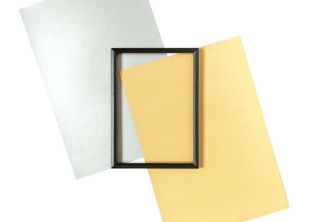 Template in a minimalistic style. Blank black photo frame and sheets of yellow and silver paper isolated on white background. Top view. Flat lay. Copy space. Stock fotó