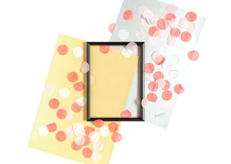 Template in a minimalistic style. An empty black photo frame and sheets of yellow and silver paper are on a white background. The mockup is decorated with round confetti. Flat lay. Copy space.