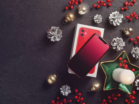 Moscow, Russia - December 12, 2019: A red iPhone 11 is on a dark cement background. Nearby are Christmas decorations. New Year holidays gift concept. Minimal composition. Flat lay. Copy space.