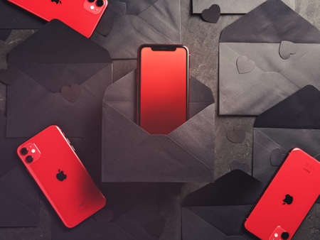Moscow, Russia - December 16, 2019: Red iPhones 11 is on a dark background with black envelopes and paper figures in the form of hearts. Minimal composition. Flat lay. Copy space. Sajtókép
