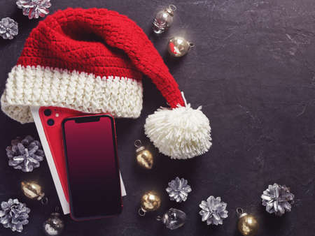 Moscow, Russia - December 12, 2019: A red iPhone 11 is on a dark background. Nearby are Christmas decorations. New Year holidays gift concept. Minimal composition. Flat lay. Copy space.