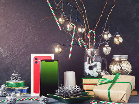 Moscow, Russia - December 19, 2019: A red iPhone 11 is on a dark background. Nearby are Christmas decorations (balls, ribbon, fir cone). New Year holidays gift concept. Copy space.