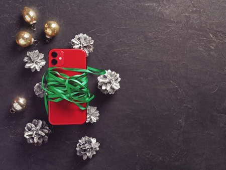 A red smartphone with two cameras is wrapped in a green ribbon and is located on a dark cement background. Nearby are Christmas decorations. New Year holidays gift concept. Flat lay. Copy space.