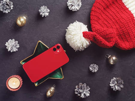 A red smartphone with two cameras is on a dark cement background. Nearby are Christmas decorations. New Year holidays gift concept. Minimal composition. Flat lay. Copy space.