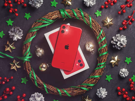 Moscow, Russia - December 16, 2019: A red iPhone 11 is on a dark background. Nearby are Christmas decorations. New Year holidays gift concept. Flat lay.