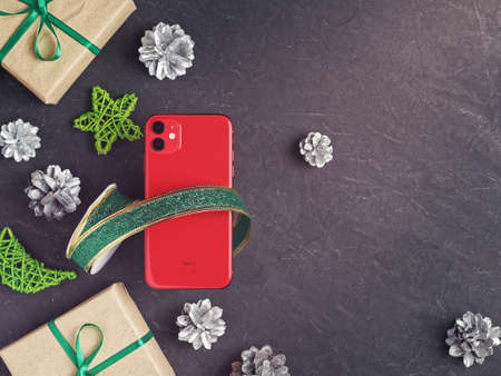 Moscow, Russia - December 17, 2019: A red iPhone 11 is on a dark background. Nearby are Christmas decorations. New Year holidays gift concept. Flat lay. Copy space. Sajtókép