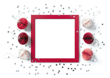 Christmas composition. Empty red wooden frame, paper Christmas decorations, star-shaped confetti are on a white background. New Year, winter concept. Greeting card. Flat lay, top view, copy space.