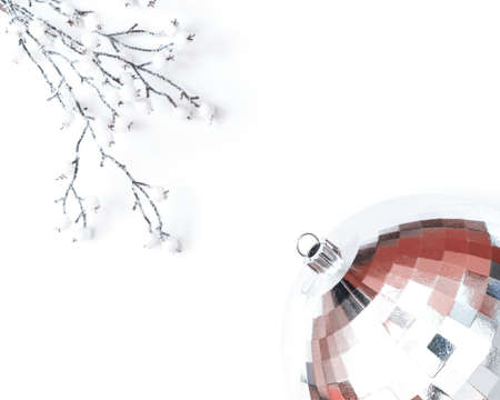 Minimalist Christmas concept. The layout is made of a snow-covered branch with white berries and a disco ball. Flat lay, top view, copy space.