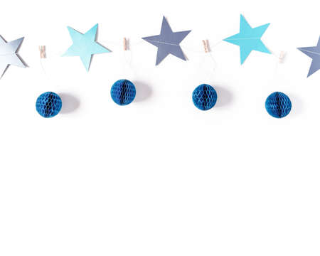 A garland of blue stars and honeycomb paper balls is on a white background. Minimalistic Christmas, new year template. Flat lay, top view, copy space.