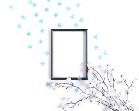 Modern winter layout made from blank black photo frame, snow covered branch and blue snowflakes. Minimalistic template for Christmas, New Year, invitation, banner. Flat lay, top view, copy space. Stock fotó