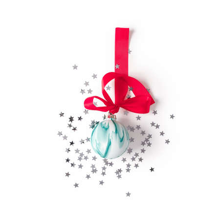 Christmas composition. A red ribbon with a bow is tied to a glass Christmas green ball. Confetti stars are scattered nearby. The concept of preparing for the new year and christmas. Flat lay.