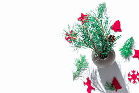 A natural pine branch with a cone is in a vase on a white background. There are red felt decorations nearby. Sunny Christmas day. Top view. Copy space. Greeting card.